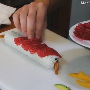 placing-pink-salmon-on-a-sushi-roll-how-to-make-sushi-rolls